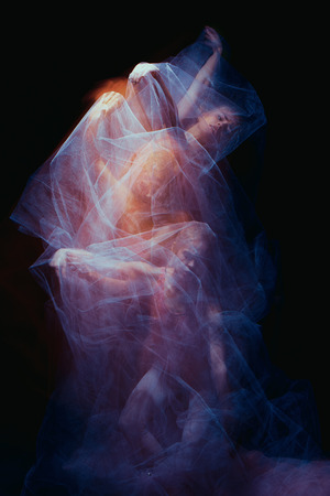 photo as art - a sensual and emotional dance of beautiful ballerina through the veil on a dark background photo