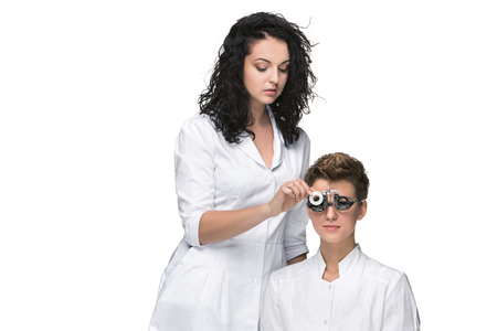 eye care professional: Optometrist examines the sight of young girl