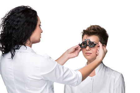 Optometrist holding an eye test glasses and giving to young woman eye examination. Isolate on white background photo