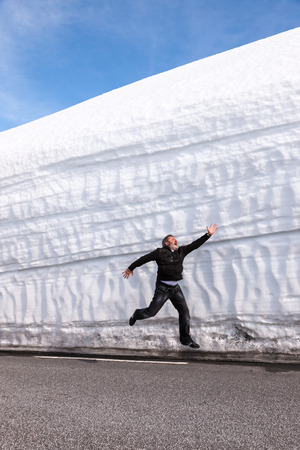 man running on the highway along the snow wall. Norway in the spring photo