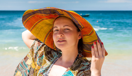 beach front: woman in hat on the beach. front view