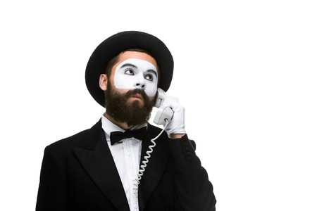 submission: man in the image mime holding a handset isolated on white background. The concept -  submission