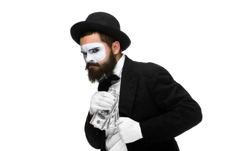 corporate greed: mime as a businessman in a  suit putting money in his pocket. isolated on a white background. concept  love of money and  greed