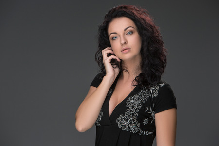 Portrait of beautiful dark-haired young woman, speaking on mobile phone against a gray background photo