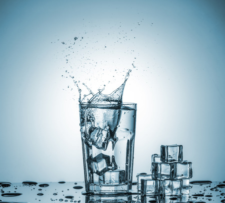 welling: ice cubes falling into a glass of water and ice cubes, lying next, on blue background