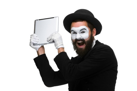 rage: mime as a businessman throws computer in rage. Isolated on white background.  The concept of despair in business. Stock Photo