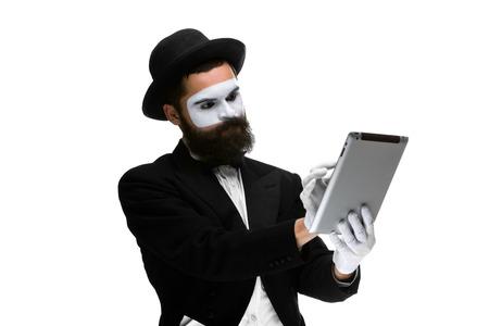 Man met een gezicht mime werken op een laptop geïsoleerd op een witte achtergrond. Concept van het denken in het bedrijfsleven Stockfoto