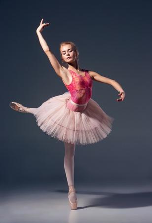 ballet: Retrato de la bailarina en actitud del ballet sobre un fondo gris. Bailarina es usar zapatos tut� rosa y de punta