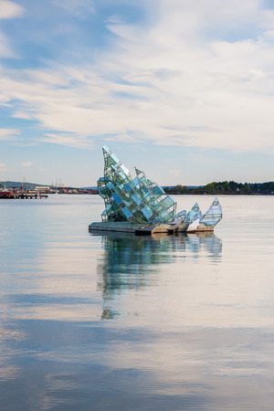 house float on water: OSLO - May 4, 2011.  She Lies is the name of a floating glass and steel construction that turns with the wind and tide, created by Monica Bonvicini May 4, 2011 near the Opera House, Oslo, Norway.