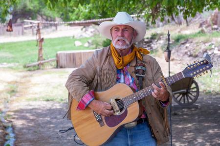 serenade: USA, Bartley Ranch Regional Park, Reno, Nevada - 14 MAY 2008. Aged man with a guitar on ranch background Editorial