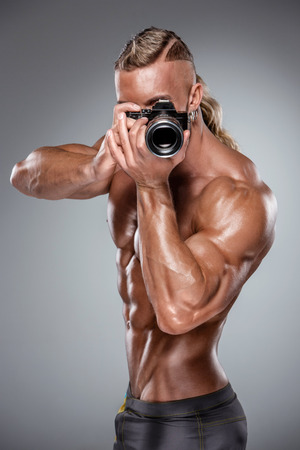 nude young: Привлекательный мужчина строитель тело, как фотографии удерживая камеру на сером фоне Фото со стока