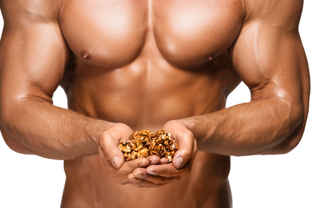 Shaped and healthy body man holding a walnuts, isolated on white background photo