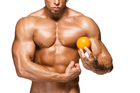 Shaped and healthy body man holding a fresh orange fruits, isolated on white background photo