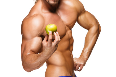 Shaped and healthy body man holding a fresh apple fruits, isolated on white background photo