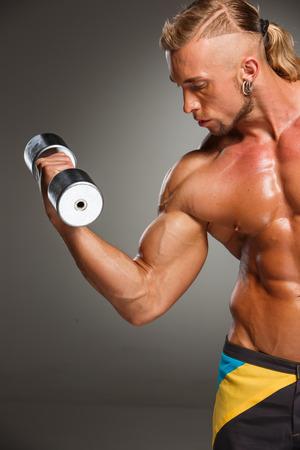 attractive male: Generador de atractivo cuerpo masculino con pesas sobre fondo gris.