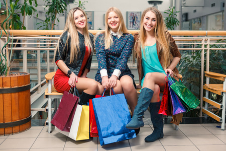 shopping, sale, happy people and tourism concept - three beautiful girls with shopping bags sitting in the mall photo
