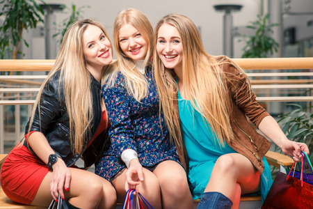 jointly: shopping, sale, happy people and tourism concept - three beautiful girls with shopping bags sitting in the mall