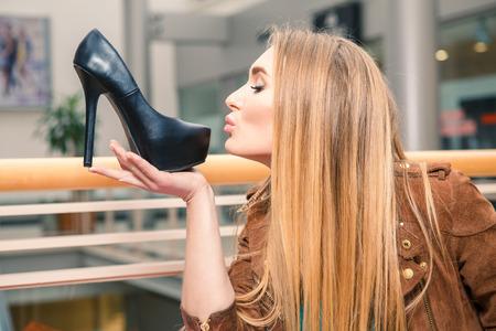 tienda de zapatos: Mujer que besa el zapato. Mujeres ama concepto zapatos. Chica rubia y zapatos de tacones altos negros sobre el fondo de la alameda. Foto de archivo