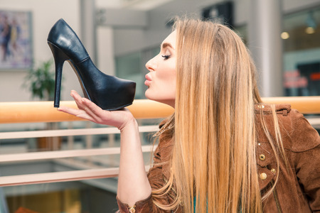 girls kissing girls: Woman kissing shoe. Women loves shoes concept. Blonde girl and black high heels shoes on the background of mall.