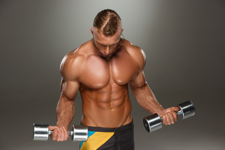 body builder: Attractive male body builder with dumbbells on gray background. Stock Photo