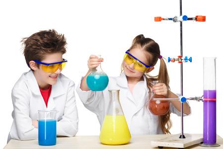 Twee schattige kinderen in scheikunde les maken van experimenten geïsoleerd op witte achtergrond