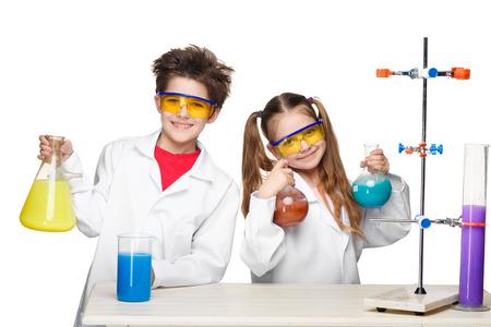 investigador cientifico: Dos niños lindos en la lección de química que hacen experimentos aislados sobre fondo blanco Foto de archivo