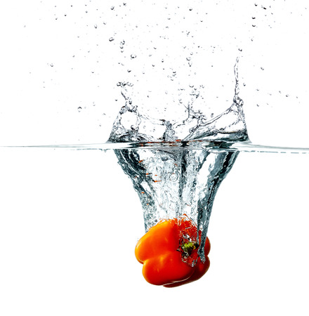 Fresh pepper drops into a water isolated on white background photo