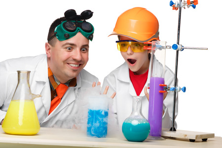 chemistry lesson: Teen and teacher of chemistry at chemistry lesson making experiments isolated on white background Stock Photo