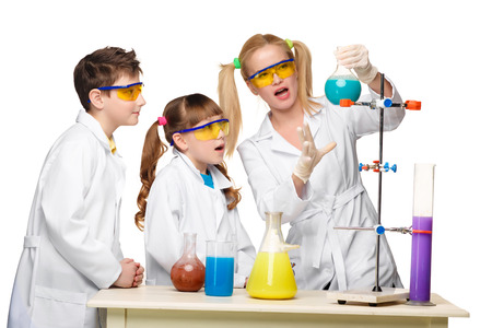 chemistry lesson: Teens and teacher of chemistry at chemistry lesson making experiments isolated on white background