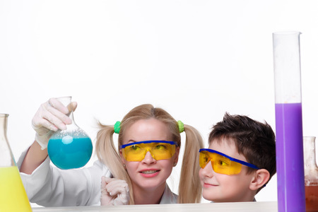 tubes: Teen and teacher of chemistry at chemistry lesson making experiments isolated on white background Stock Photo