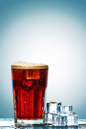 carbonation: Glass of cola with ice cubes on a blue background