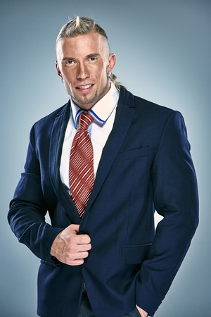 Portrait of an attractive young businessman wearing blue suit. Blonde hair. On blue background photo