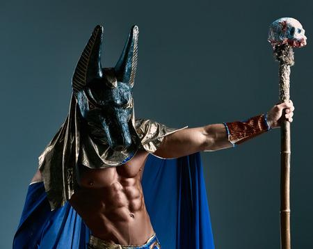 De man in het beeld van de oude Egyptische farao met een masker van Anubis op zijn gezicht op een blauwe achtergrond Stockfoto