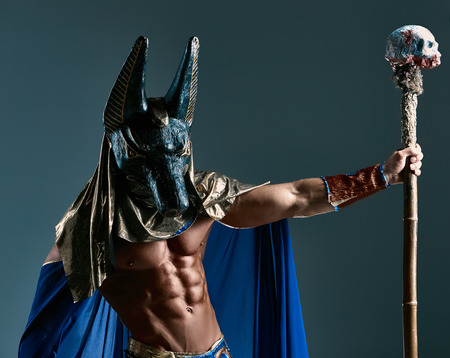 costumes: The man in the image of the ancient Egyptian Pharaoh  with a  mask of  Anubis on his face on blue background