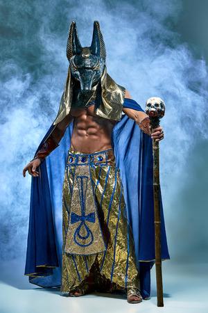rey: El hombre en la imagen del antiguo faraón egipcio con una máscara de Anubis en su rostro sobre fondo azul Foto de archivo