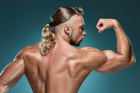 naked male body: torso of attractive male body builder on blue background. Stock Photo