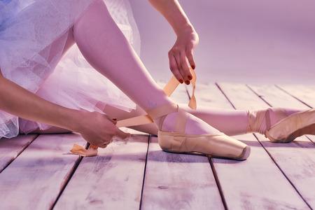 Professionelle Ballerina, die sich ihre Ballettschuhe auf dem Holzboden auf einem rosa Hintergrund. Füße close-up Lizenzfreie Bilder