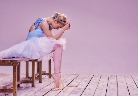 Tired ballet dancer sitting on the wooden floor on a pink background Фото со стока
