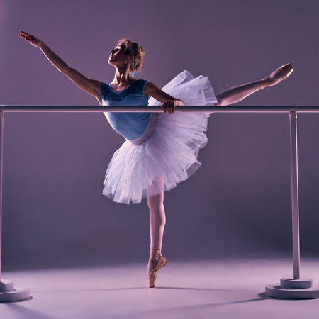 ballet bar: classic ballet dancer in white tutu posing on one leg at ballet barre on a lilac background Stock Photo