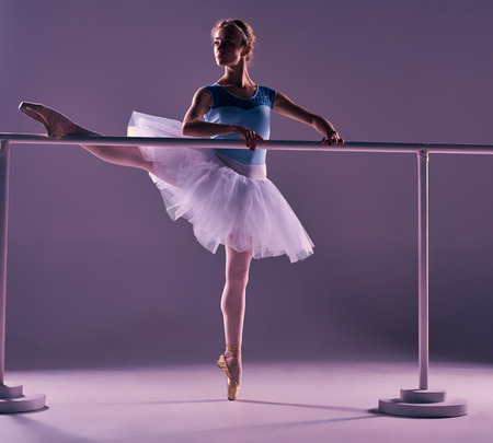 barre: classic ballet dancer in white tutu posing on one leg at ballet barre on a lilac background Stock Photo