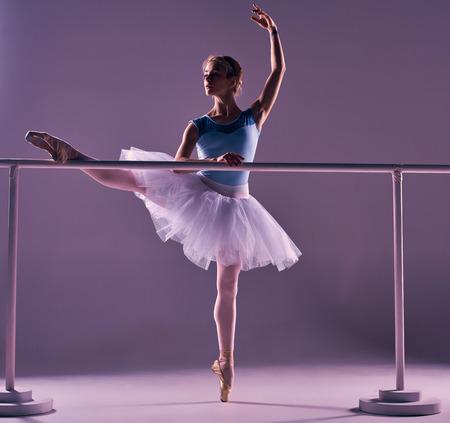 ballet ni�as: bailarina de ballet cl�sico en el tut� blanco posando en una pierna en barra de ballet en un fondo de la lila