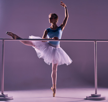 ballet tutu: classic ballet dancer in white tutu posing on one leg at ballet barre on a lilac background Stock Photo