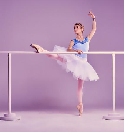 ballet: bailarina de ballet cl�sico en el tut� blanco posando en una pierna en barra de ballet en un fondo de la lila