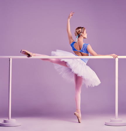 classic ballet dancer in white tutu posing on one leg at ballet barre on a lilac background Фото со стока