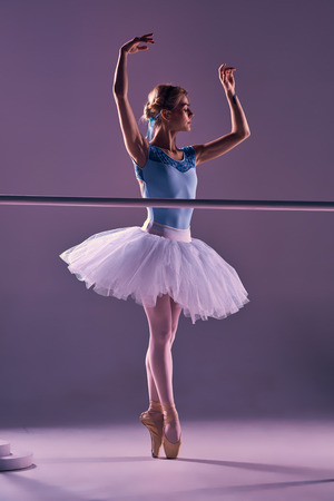 barre: classic ballet dancer in white tutu at ballet barre on a lilac background
