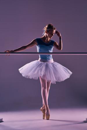 ballet: bailarina de ballet cl�sico en tut� blanco en barra de ballet sobre un fondo de color lila