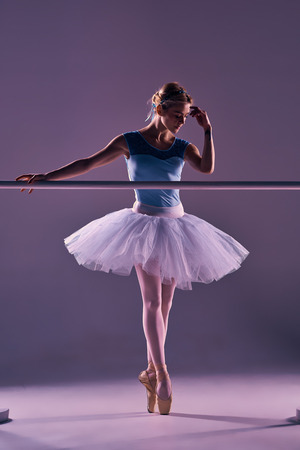 ballet bar: classic ballet dancer in white tutu at ballet barre on a lilac background