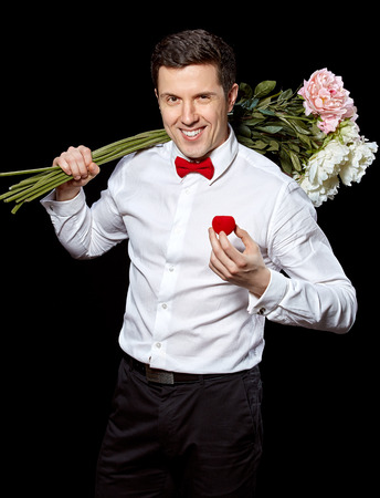 The elegant man in a white shirt and red butterfly  holding a box with wedding ring and flowers on black background photo
