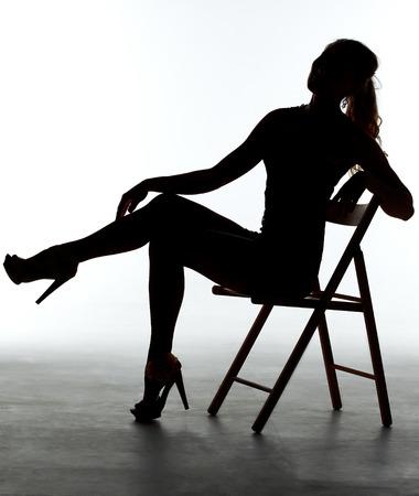 sexy beine: Mädchen in einem glänzenden Kleid, das auf Stuhl sitzt. Silhouette auf weißem Hintergrund