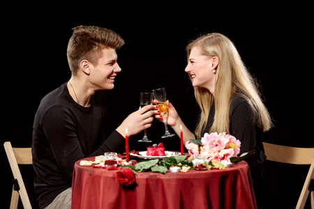 romantic evening with wine: Portrait Of Romantic Couple Toasting white Wine At Dinner  on black background Stock Photo